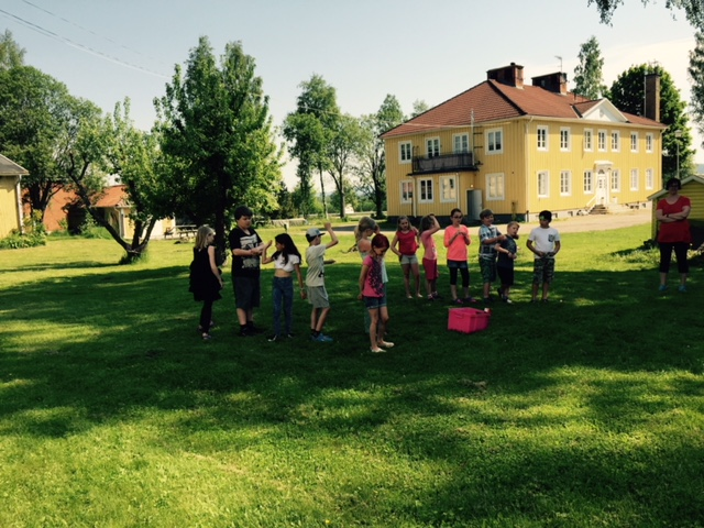 Människor utför aktiviteter utanför den gula vandrarhemsbyggnaden.